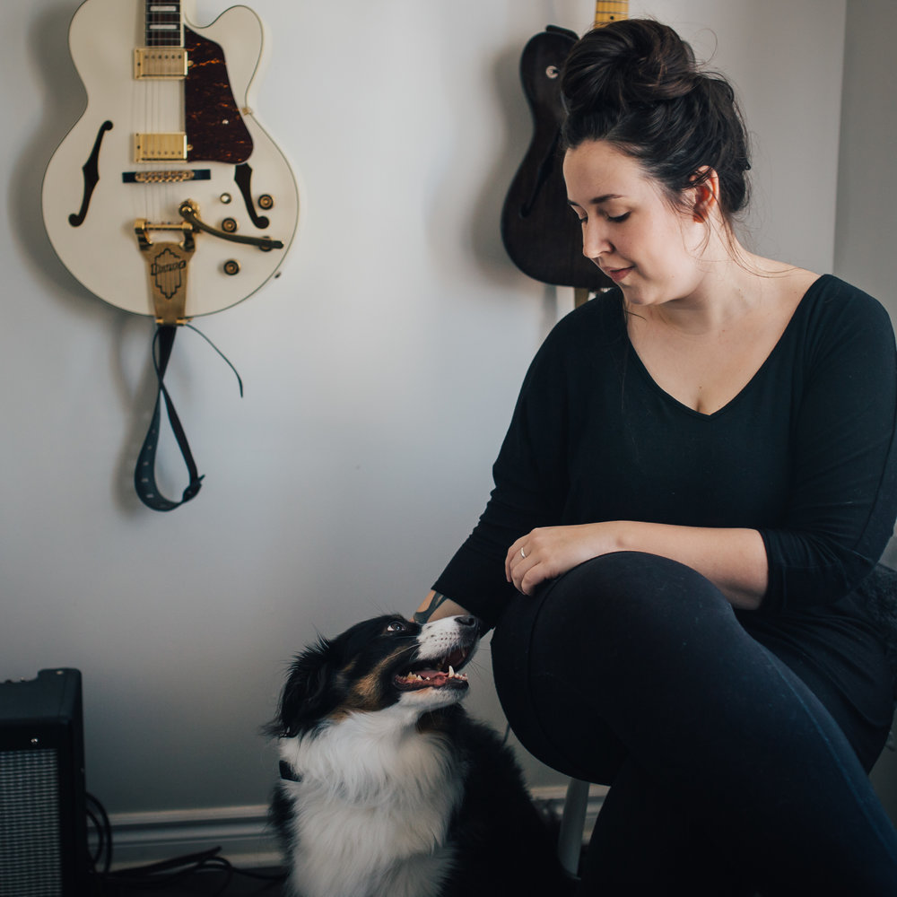 Kate is seated in front of a wall with two guitars. She is looking down at her dog.