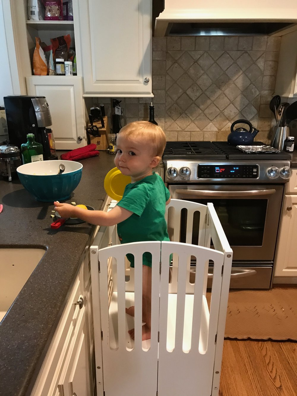 This is a blog post about my one-year-old wielding a deadly weapon, and no, I don't have any photographic evidence. This is a picture of the same toddler on the same stool holding a spoon. Use your imagination.