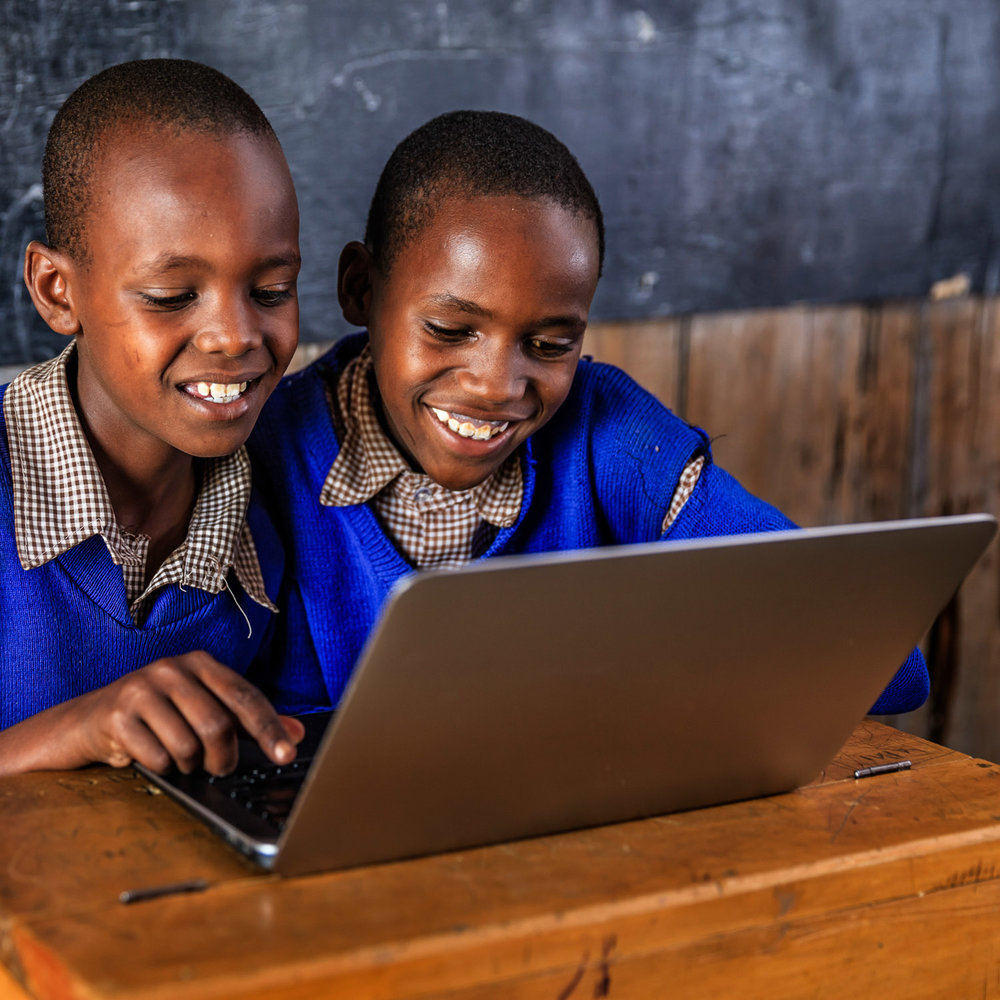 African children using a laptop inside classroom in very remote school. There is no light and electricity inside the classroom. School is located in very remote area in southern Kenya. Image credit: Bartosz Hadyniak/Getty Images