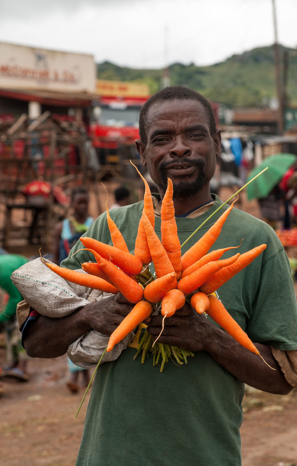 Farmer selling carrots at Lusulu Market, Malawi & Mozambique Border, March 2011. Photo credit: Sheridan Jones McCrae ©