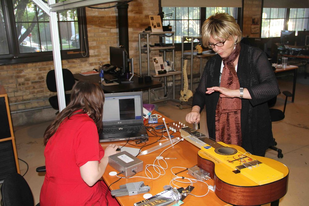 Serap Bastepe-Gray, a Peabody guitar faculty member who holds a joint appointment in Neurology at the School of Medicine, tests the SmartGuitar, an instrument she designed to measure how much force a musician applies to the fretboard, with the goal of learning more about the playing-related musculoskeletal disorders of musicians. Image credit: Innovative Sports Training, Inc.