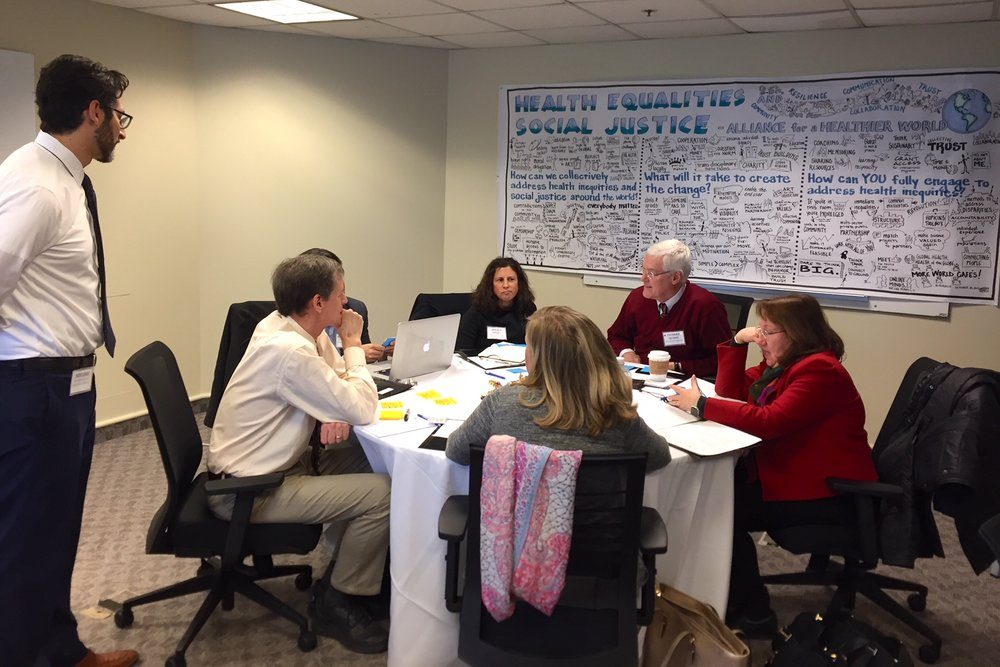 Group discusses health equity program priorities for the Alliance for a Healthier World.  Pictured (L-R)   Ben LInk (standing),   Peter Winch, Kathleen Grealish (backwards), Toni Ungaretti, Tom Quinn, Jess Fanzo, Anthony So (obscured), Photo by Sheridan Jones McCrae.