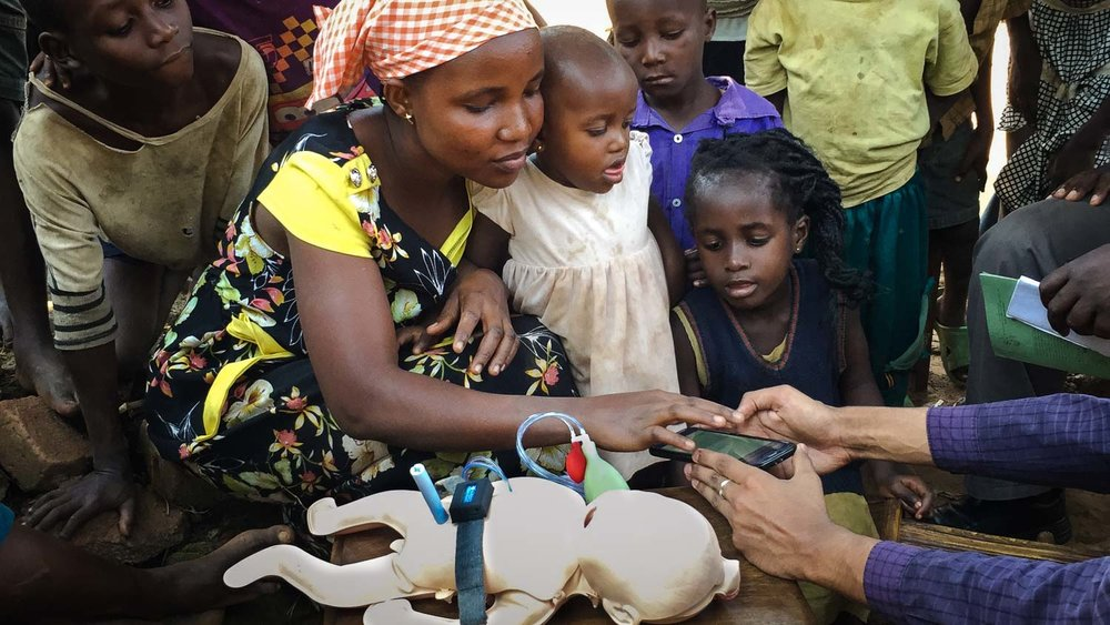 Mother learns new system. Students of Whiting School of Engineering's Center for Innovation & Design conduct field work in communities. Team NEMO (Empowering Mothers to Identify Neonatal Illnesses) works closely with communities to develop new products and systems.  Photo credit: Polly Ma, August 2016