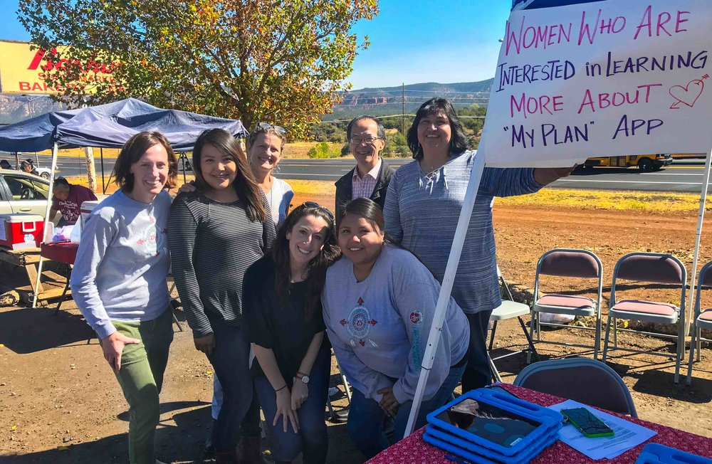 Research investigators and stakeholders Emily Haroz, Rayann Chee-Amos, Allison Barlow, Breann Clarkson, Tak Igusa, Lauren Tingey, Francene Larzelere (Left to right) gather at an interview site in a parking lot on the White Mountain Apache reservation in November 2017 to test women's response to the new app. Photographer unknown.