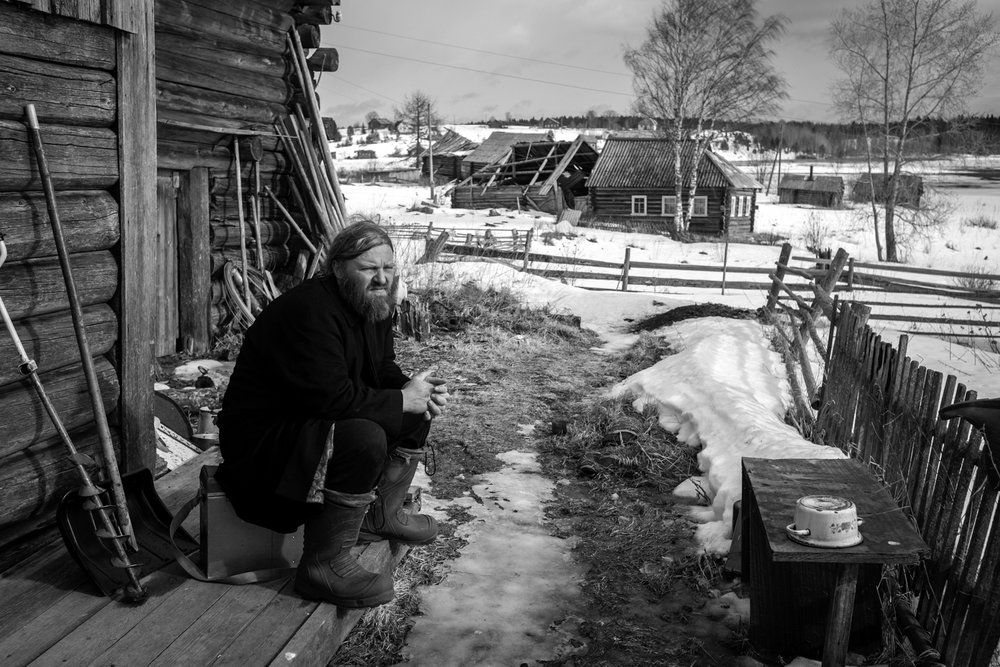 The priest Arkadiy is sitting on the porch of rural house and basking in the spring sun