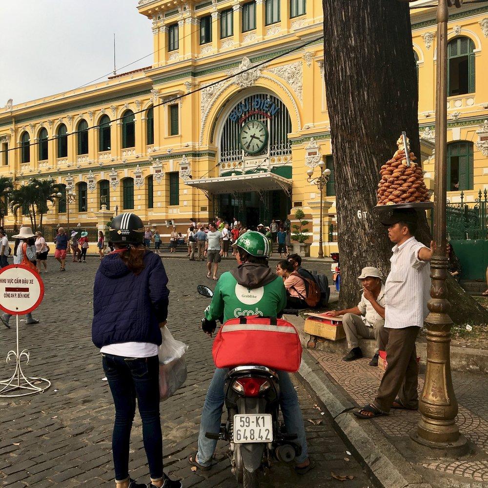 Street vendor & Grab driver near main entrance of Saigon Central Post Office / Ho Chi Minh City / ©2017 Melody Jean Moulton