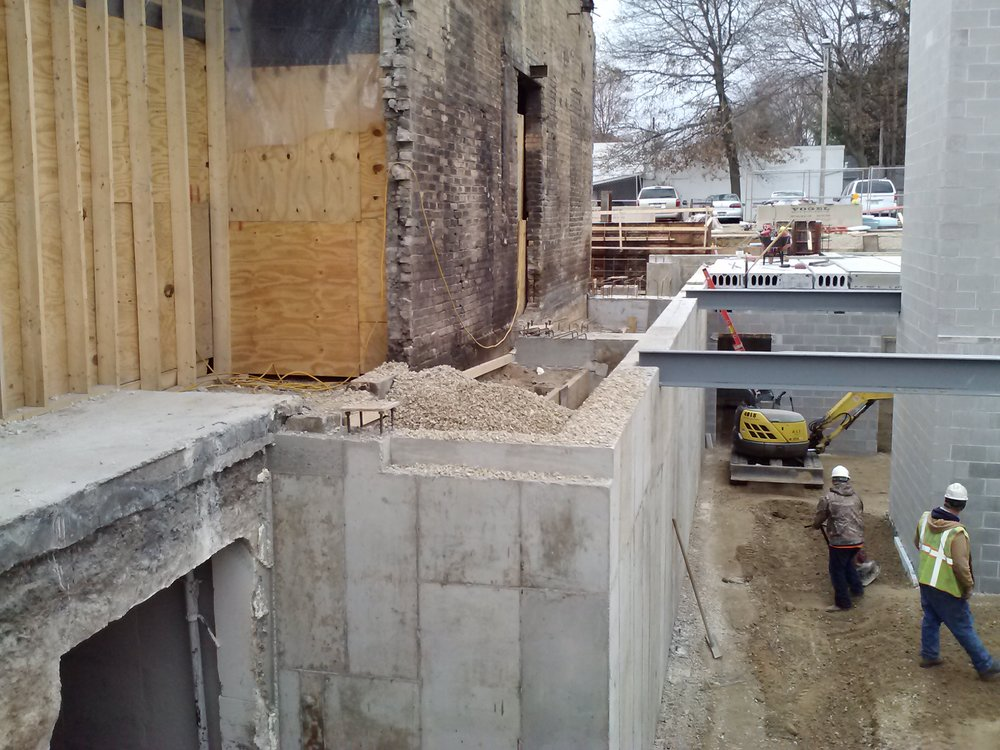 This photo shows where the historic structure meets the new addition, foundation walls for the basement before the precast plank is installed, the elevator shaft is to the right and the new concrete opening to the existing basement is to the left.