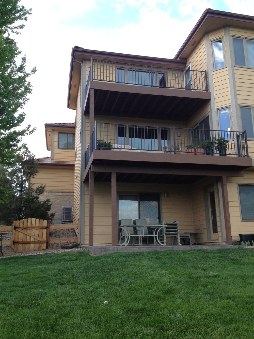 second and third story decks above stamped concrete in parker, co  After the existing concrete patio was removed, a new stamped concrete patio was constructed. These decks were then built with TimberTech decking and Fortress Fe26 railing.