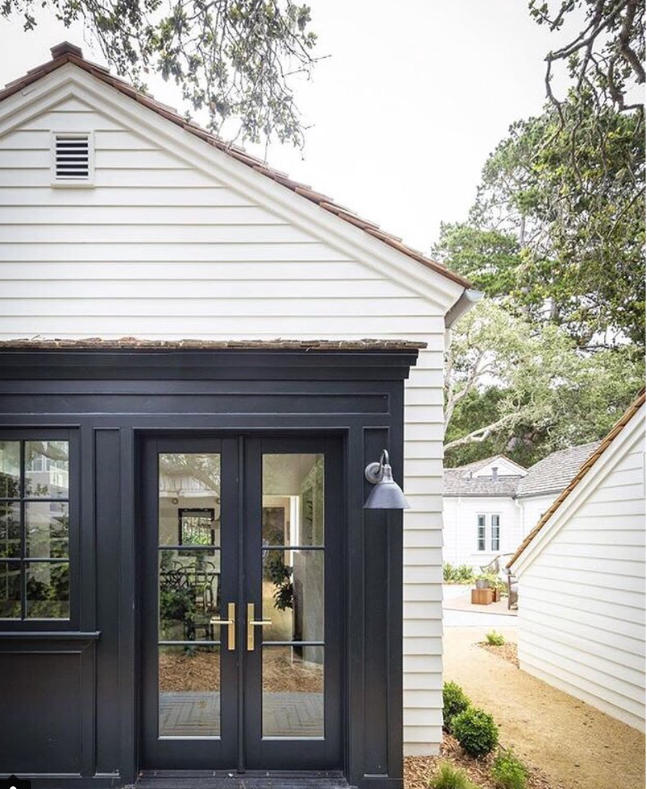 white cottage with black doors