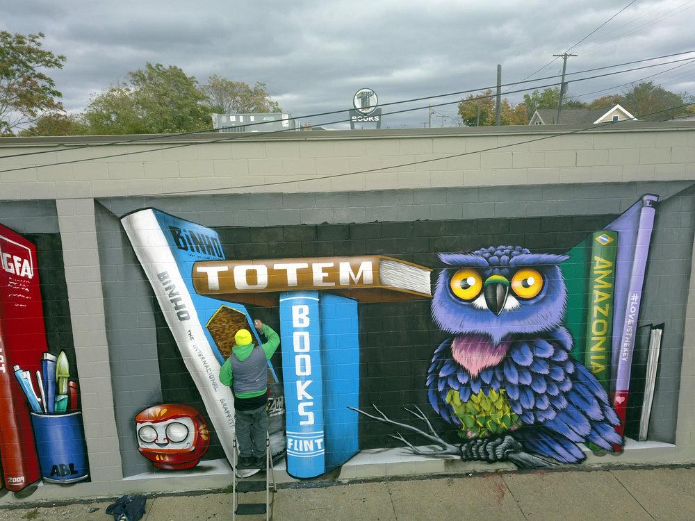 brazilian artist and graffiti legend, binho ribeiro, adds finishing details to his literary themed mural at totem books.