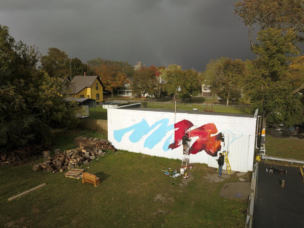storm clouds cast a trace rainbow over the flint skyline as meggs continues his piece. flint public art project executive director joe schipani regards with approval.