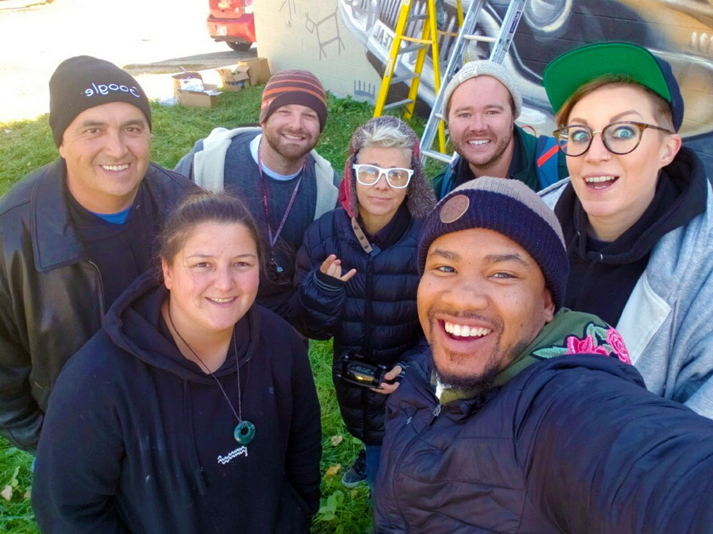 """the flint fam gathers post rainfall to finish painting and documenting the new murals. from left to right: joe schipani, hayley """"aylo"""" garner, kevin """"scraps"""" burdick, zippy downing, christopher mcgeorge, trevor norman, & joy """"cbloxx"""" gilleard."""