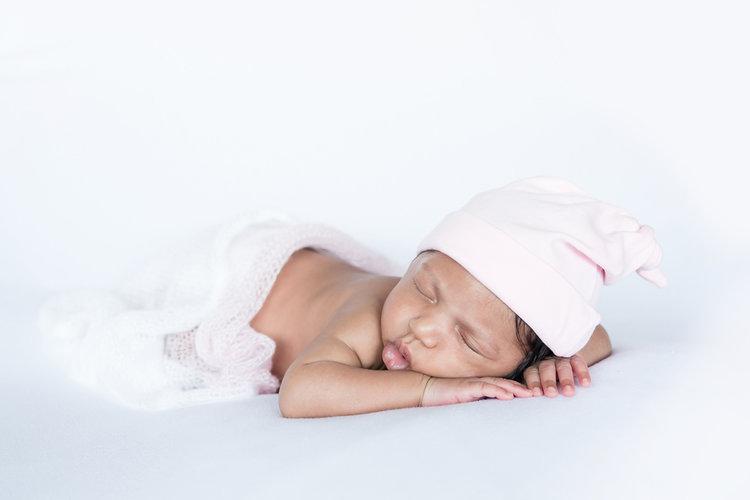 Newborn baby girl sleeping wearing a pink hat