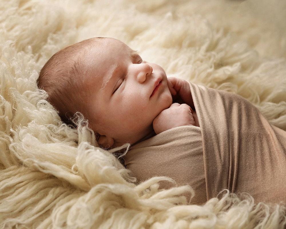Newborn baby boy swaddled in a brown wrap on a fur rug
