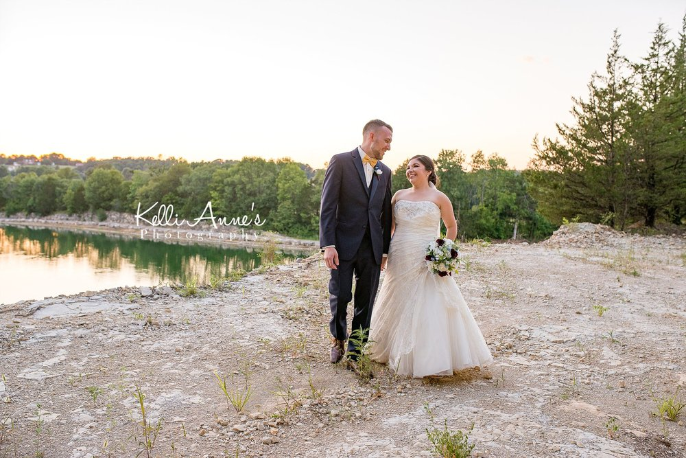 Bride and Groom, Portrait, Walking, Looking at each other, Outlook point, bluff, sunset, cedar, rocks, yellow bow tie, romantic, sunset bluffs, washington mo