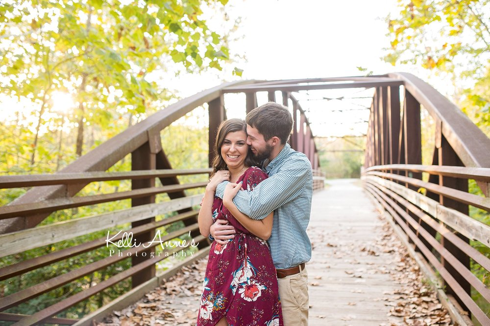 Engagement Session, Fall, Capen Park, Columbia MO, woods, warm, sun kissed, sunset, Trees, Floral Dress, Rust, bridge, laughing, leaves, romantic