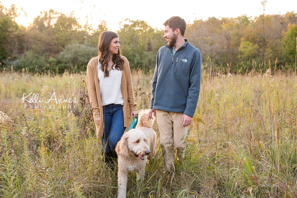 Engagement Session, Fall, Capen Park, Columbia MO, field, blanket, plaid blanket, woods, warm, sun kissed, sunset, Trees, Floral mustard sweater, jeans, boots, walking, laughing, goldendoodle