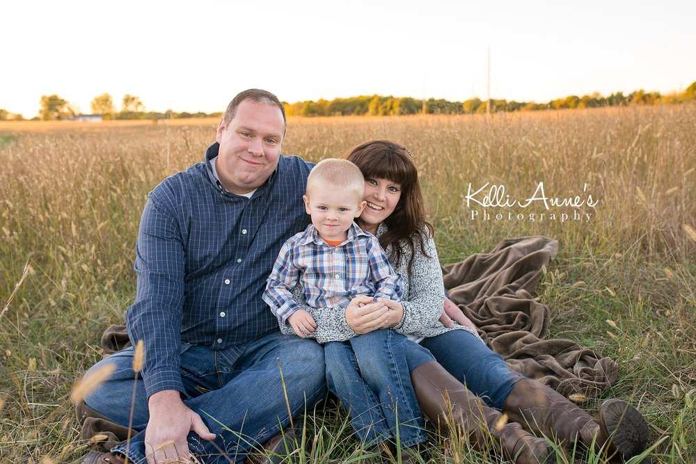 Family of 3, little boy, mom, dad, sitting, brown blanket. field, tall grass, sunset, golden light, trees, fellows lake, springfield mo