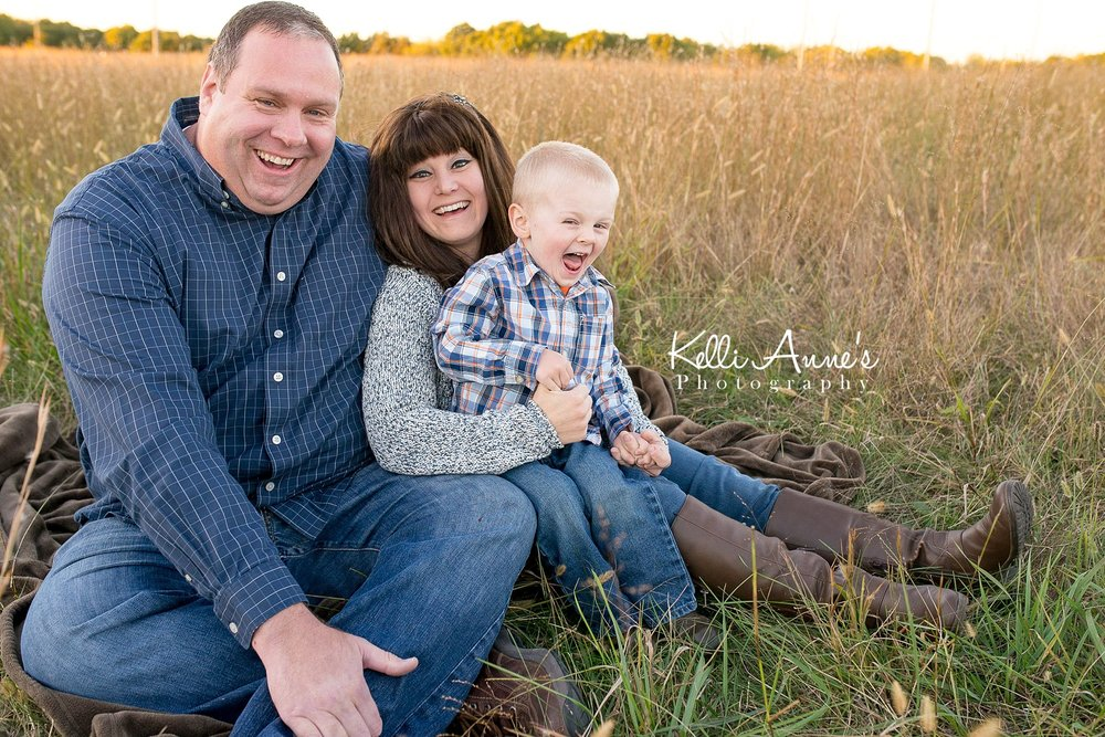 Laughing, family of 3, sitting, brown blanket, fall, fall colors, brown, tan, blue, black, white, grey, orange, mom, dad, little boy, 3 year old, jeans, sunset, fellows lake, springfield mo