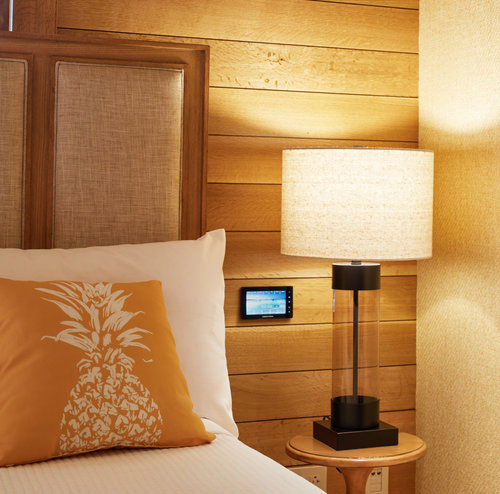 Edge of queen bed with white linens and wooden walls and nightstand with lamp and touchscreen room control monitor beside bed