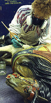 The horse's face is brown from layers of darkened varnish. Removing varnish revealed the original light gray paint, as seen on the leg, where the volunteer is applying a new small patch of solvent.