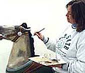 After applying a barrier coat, Linda McDonald touches up the paint on a small horse.