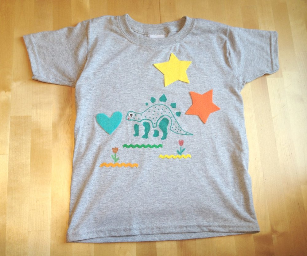 Easy-Tee-sy, t-shirt design- ages 5 and up  - Have you been searching for a t-shirt with a robot, a dinosaur, and a bunny on it? Not so easy to find, but you can make it!  Kids will use stencils, fabric markers, felt appliques, sparkles, pompoms, google eyes and trims to design a unique and one of a kind t-shirt.