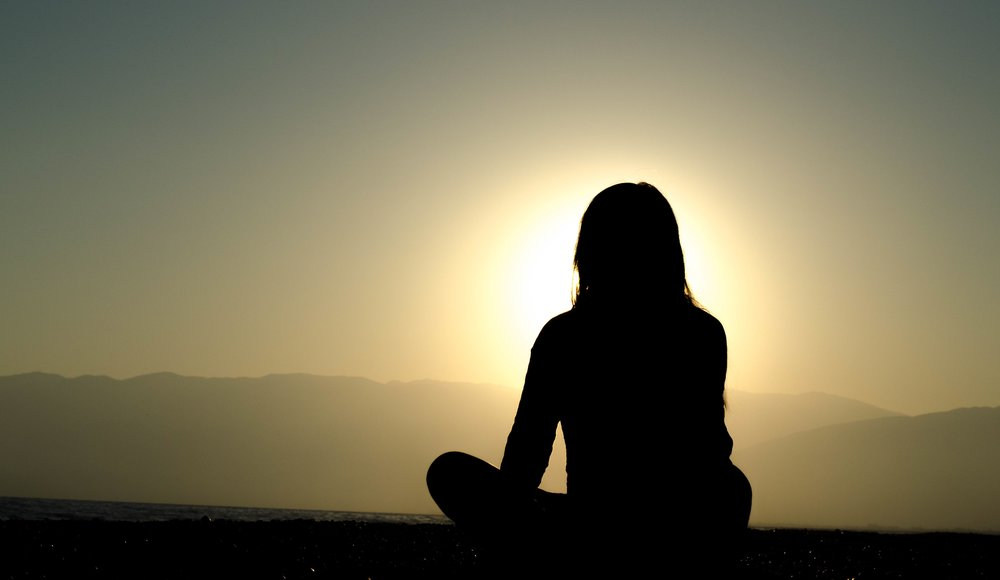 Woman sits and meditates in front of setting sun