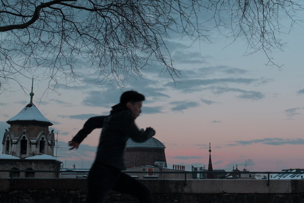 Boy runs past buildings in the dusk