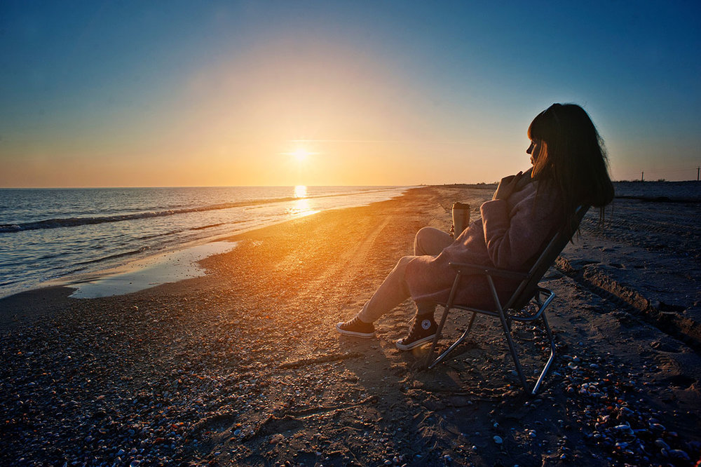 Woman sits on chair at beach during sunset
