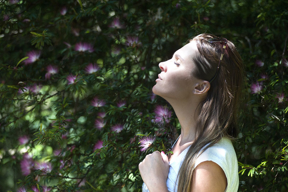Woman practices meditation in open air garden