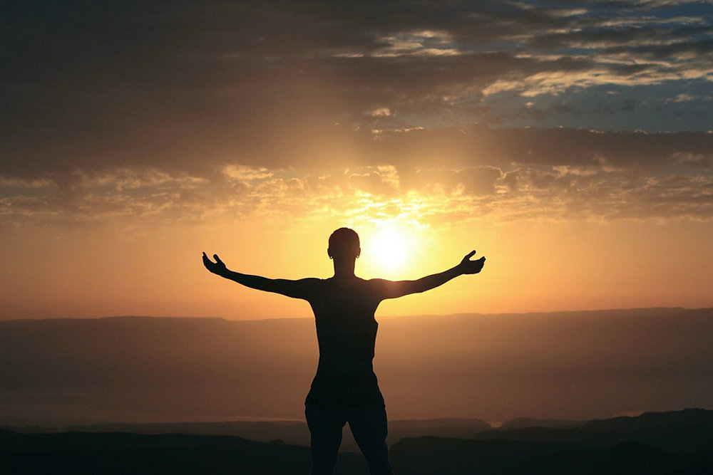 Man stands with arms held open in front of setting sun