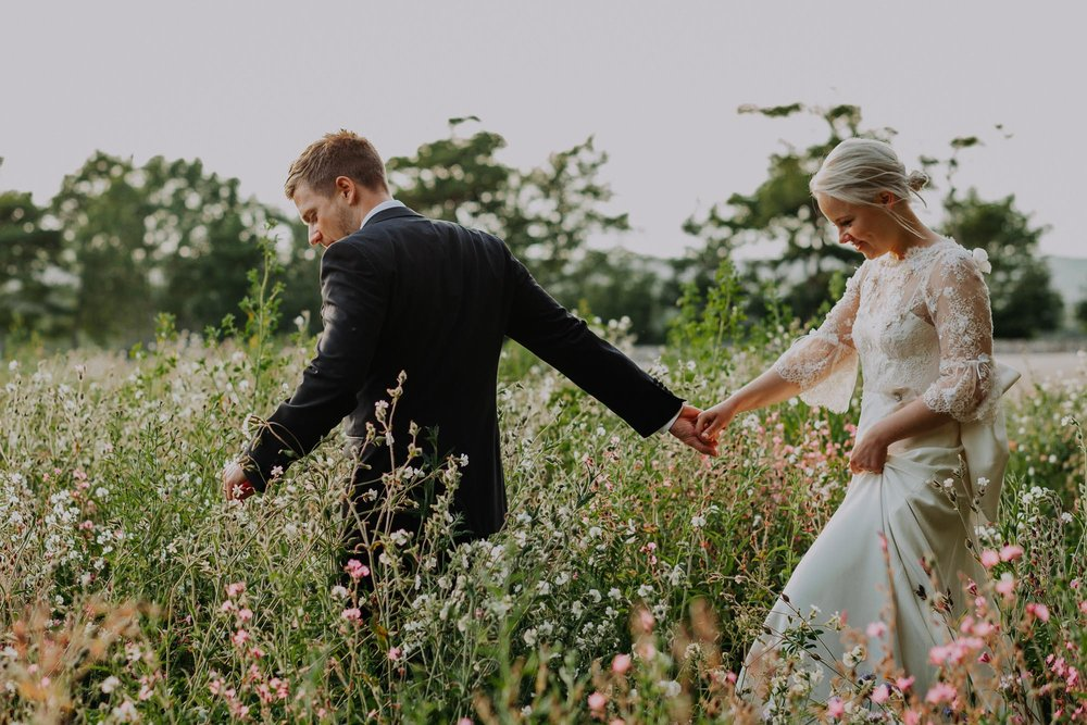 field of flowers holding hands wedding dress