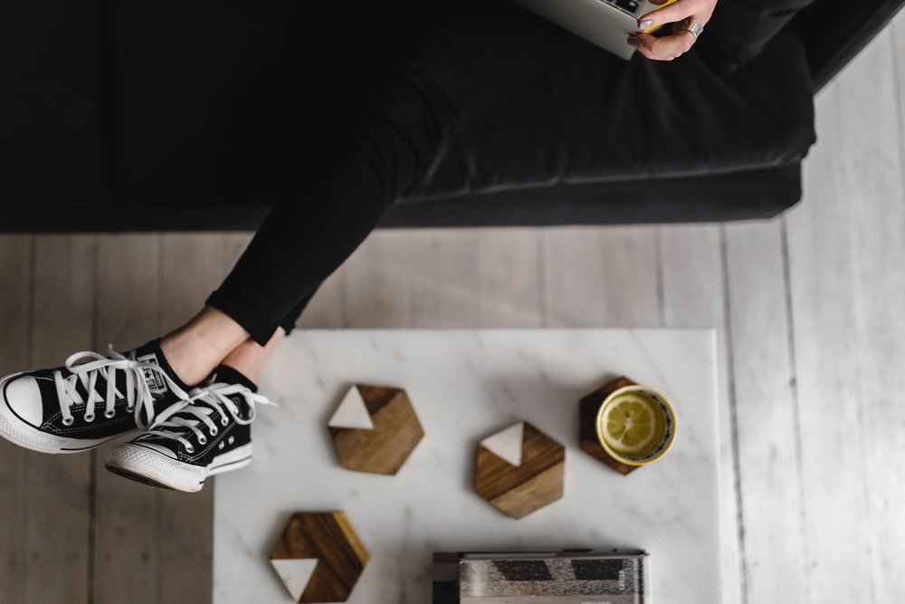 kaboompics_Woman with legs on the coffee table, wearing converse sneakers and working on her laptop.jpg