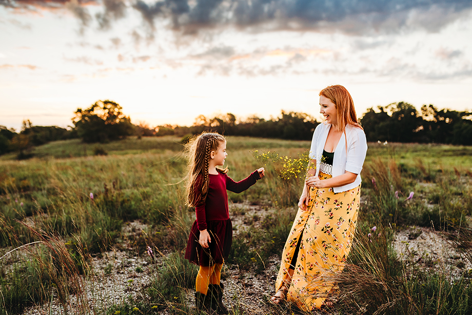 GirlGirl gives mom flowers during Fort Worth family photographer session at sunrise.