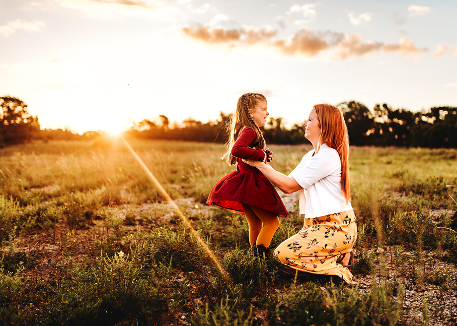 Mom tickles daughter as the sunrises over a hill in the beautiful Lyndon B Johnson Grasslands in Decatur Texas.  Moment is captured by Fort Worth Photographer Jeennie Elissa
