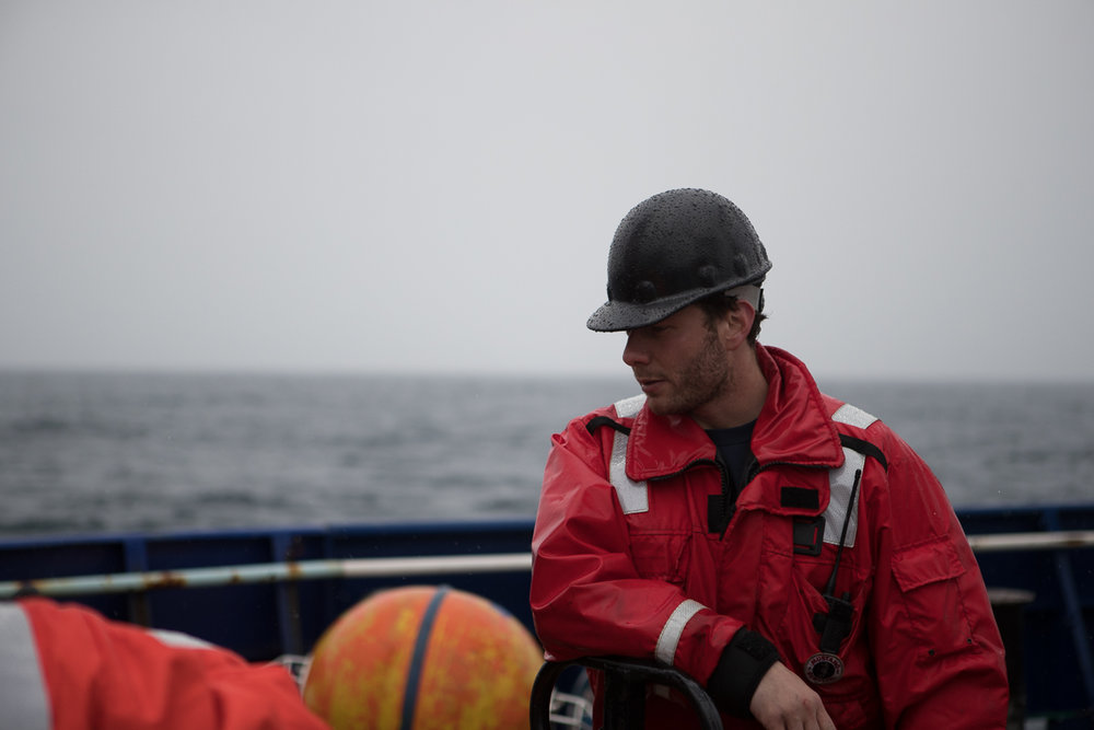 Ethan Roth observes some of the mooring equipment splayed out on the aft deck of R/V  Sikuliaq . Photo credit: Brendan Smith