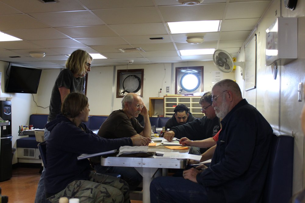 Scientists gather in the galley, discussing the logistics of sampling in the coming days. Left to right: Catherine Berchok, Libby Logerwell, Chris Wilson, Armando Urrutia, Geoff Lebon, and Captain Pete Hall. Photo credit: Harmony Wayner