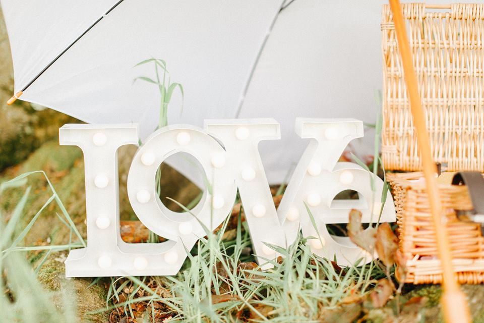 Love sign wedding decoration at wedding reception party with white umbrella on grass