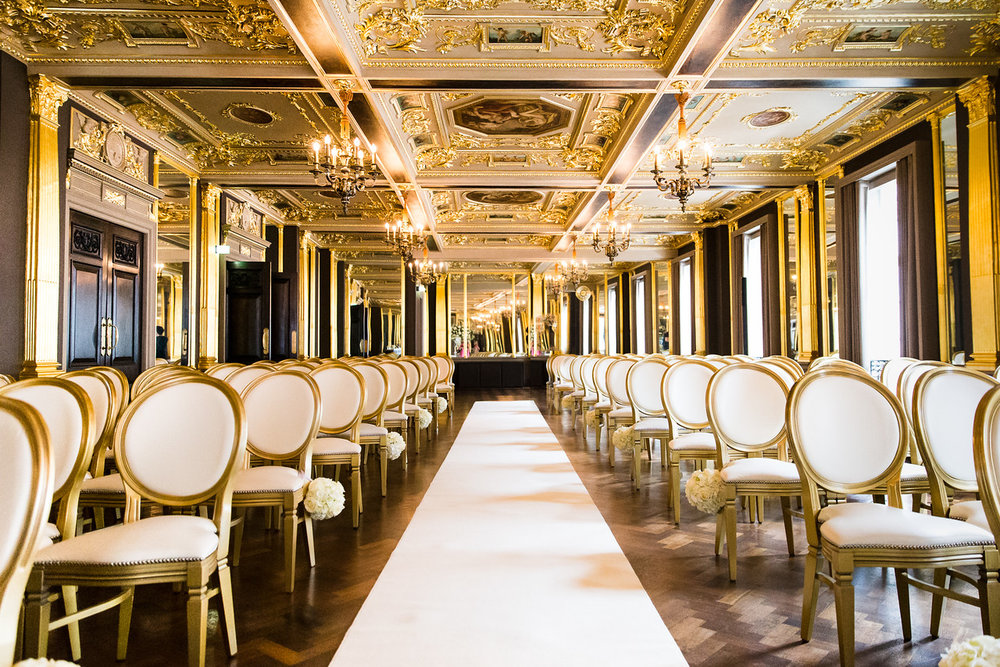 Wedding Ceremony ready and set up. Gold wedding chairs and white aisle runner in Hotel Cafe Royal