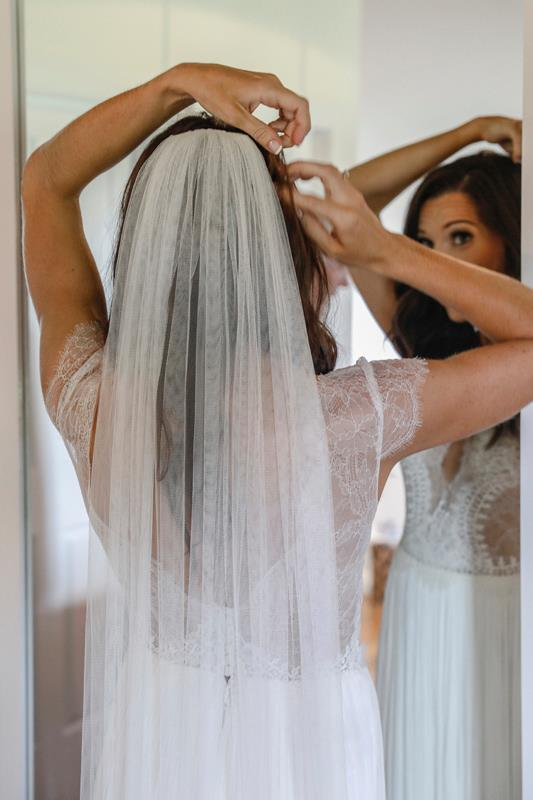 Bride putting in veil before wedding