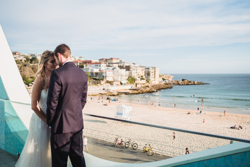 Bride and Groom looking over Bondi Beach on their wedding day from North Bondi Surf Club