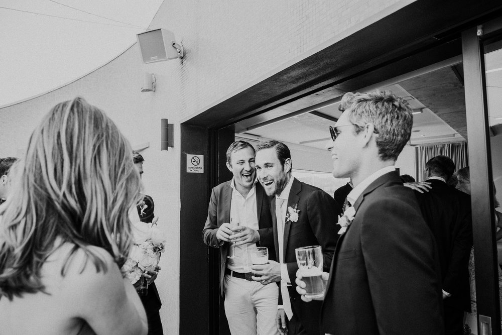 Groom laughing with wedding guests at North Bondi Surf Club Wedding
