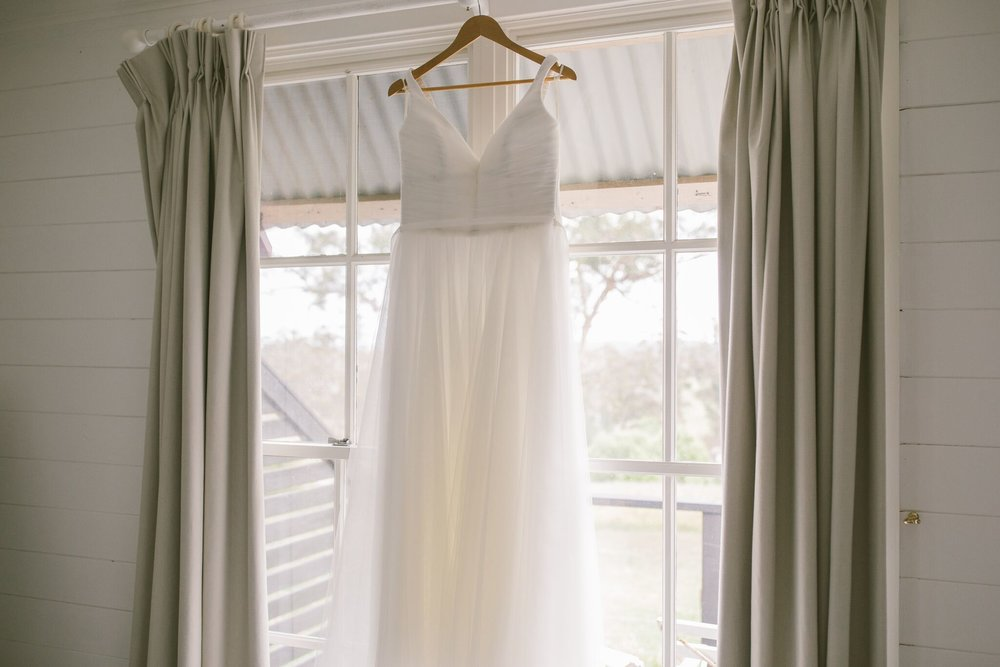 Wedding dress hung up on a window in Mali Brae Farm Wedding