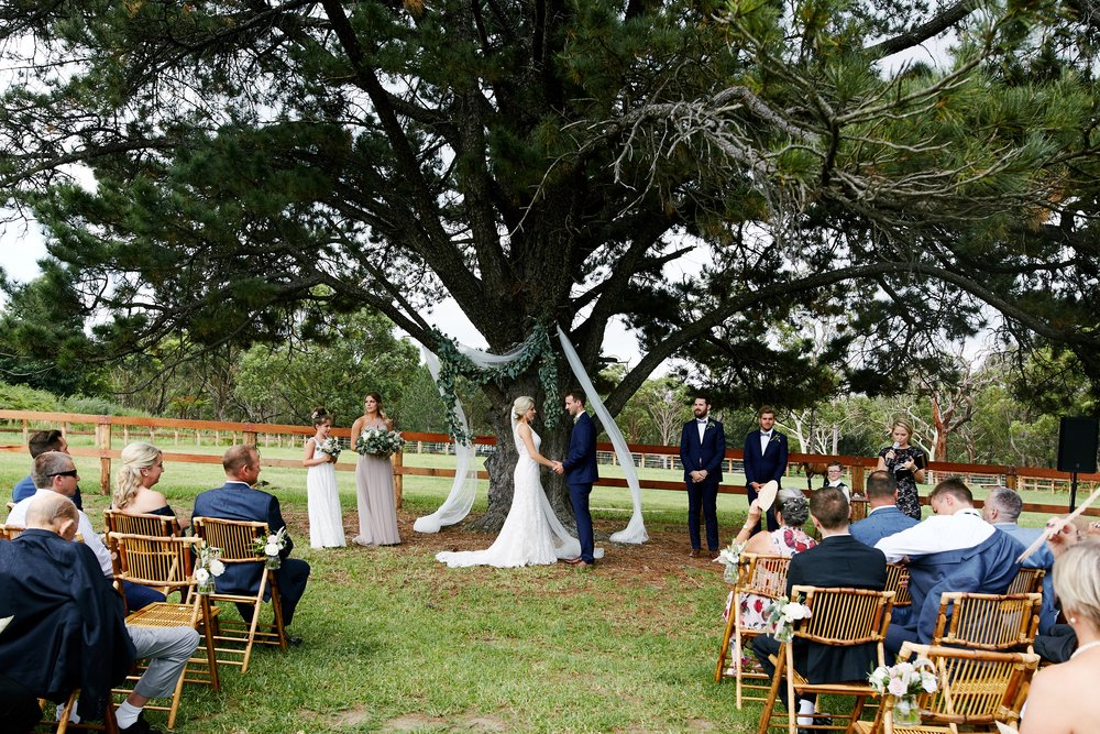 Beautiful outdoor wedding ceremony. Bride and groom looking at each other as they get married underneath a tree at the NSW Central Coast wedding venue The Stables of Somersby