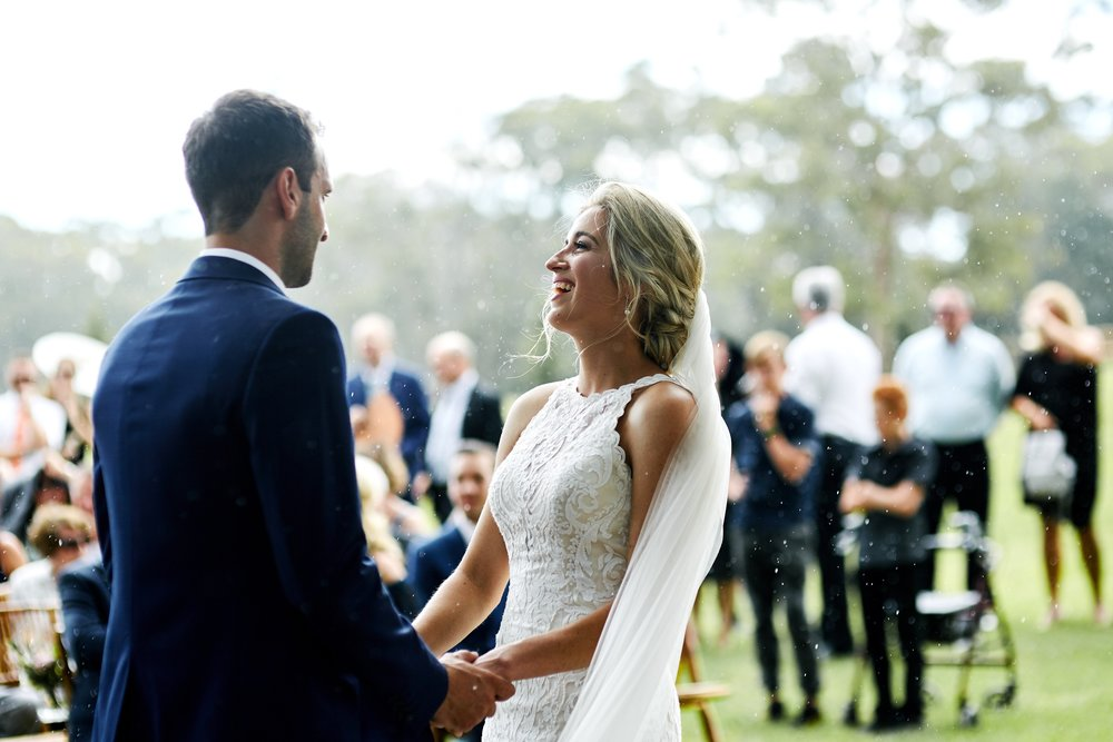 Bride and Groom laughing in the rain at their wedding ceremony in the Central Coast