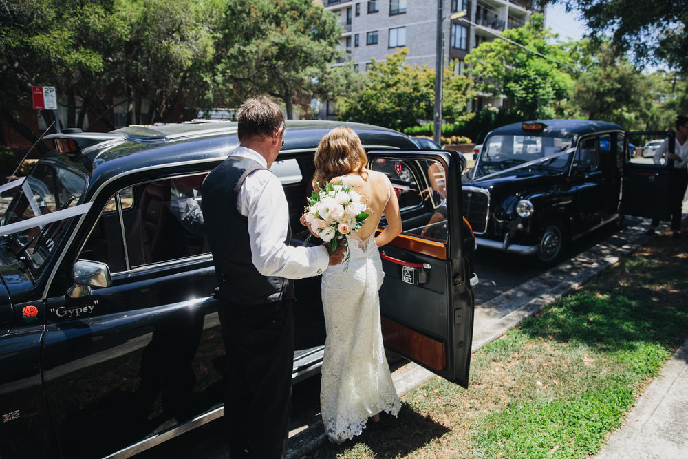 Bride getting into her wedding car a London taxi