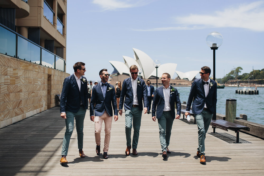 Groom and groomsmen walking by the Sydney harbour laughing on their way to the wedding. Sydney Opera house in the background of the shot.