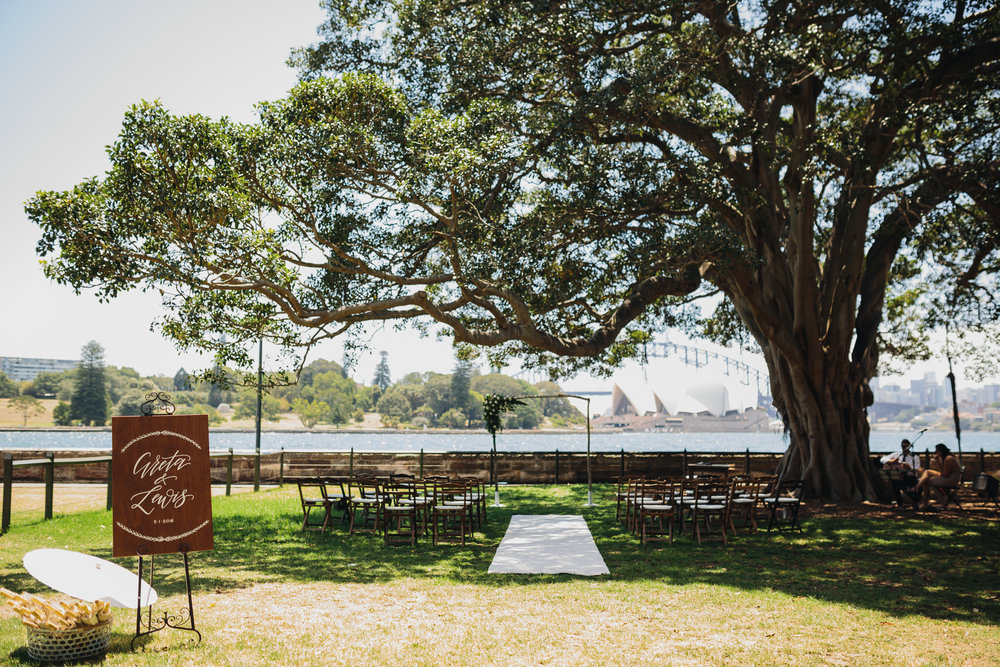 Wedding Ceremony set up at The Sydney Botanic Gardens. Wedding arbour with white flowers, wedding guest chairs, wedding sign. Wedding Ceremony location is on the grass Harbour View Lawn wedding infront of the Sydney Opera house and Sydney Harbour Bridge.