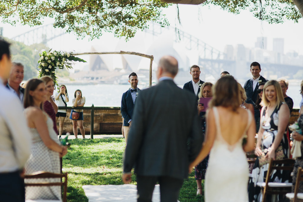 Bride walking down the aisle and groom smiling with the view of the Sydney Opera House and Sydney Botanic Gardens in the background